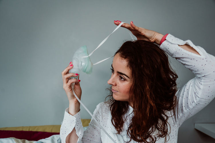 Woman wearing oxygen mask while sitting on bed against wall in hospital