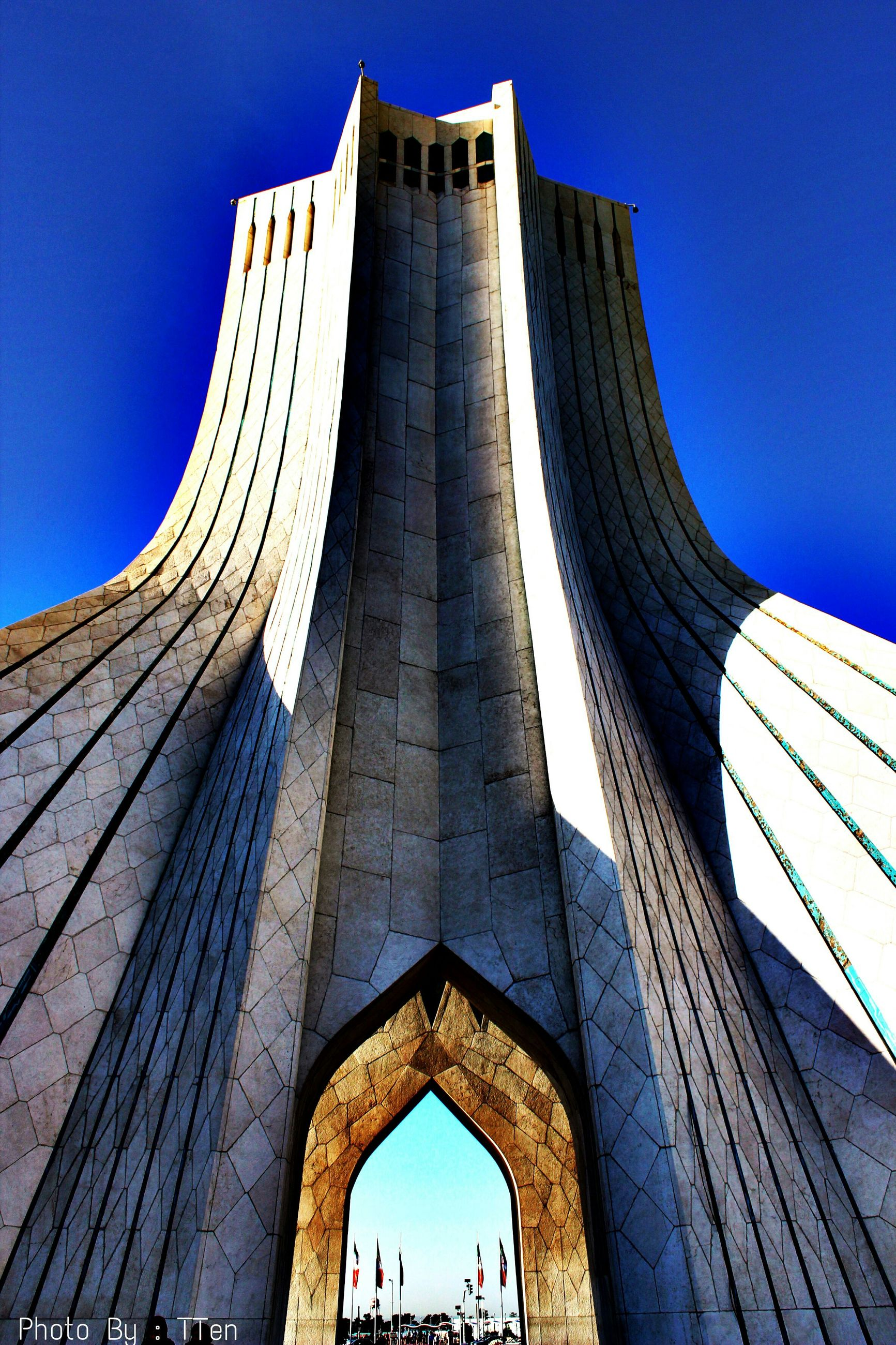 architecture, built structure, low angle view, building exterior, famous place, tower, tall - high, international landmark, modern, travel destinations, skyscraper, tourism, capital cities, city, clear sky, travel, arch, blue, office building, sky