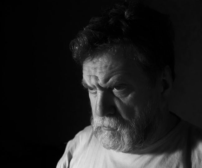 Angry mature bearded man against black background
