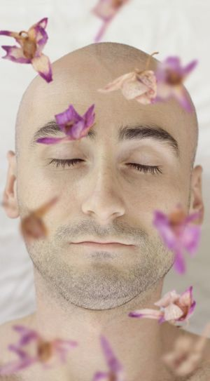 Close-up of mid adult man with eyes closed relaxing in spa