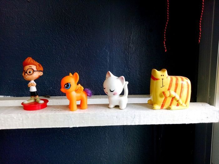 Close-up of toys on table against wall