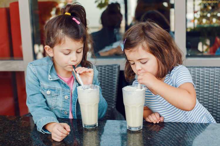 Sisters drinking milk in cafe