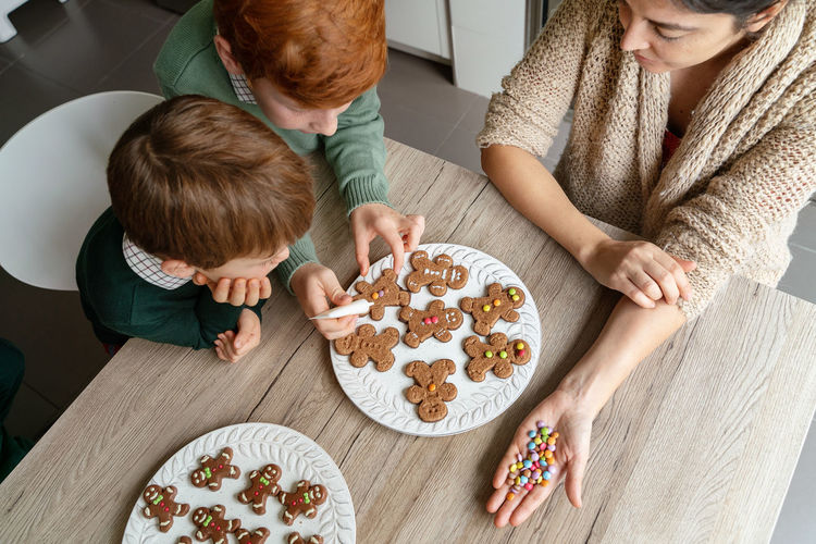 High angle view of mother with kids preparing cookies at home
