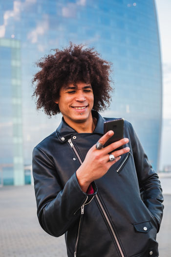 Smiling young man using smart phone