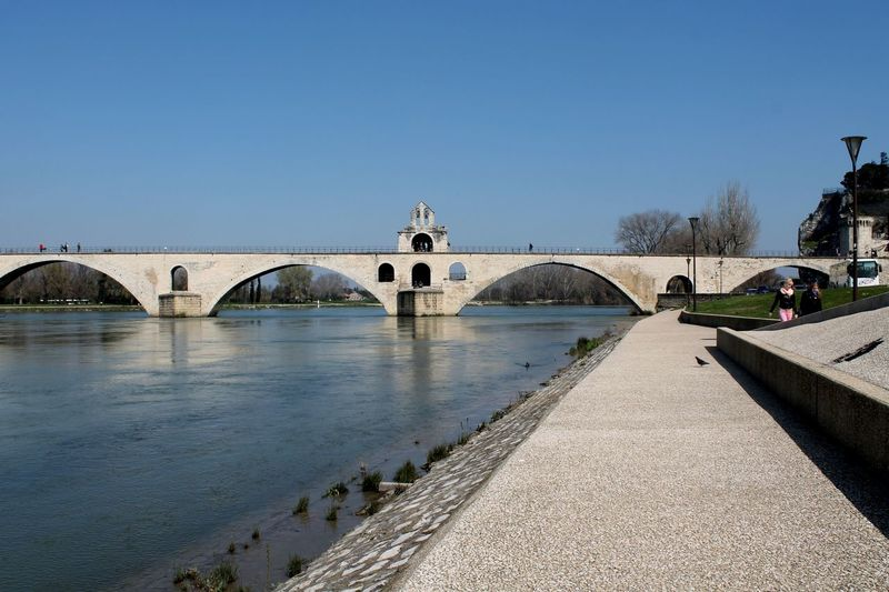 Bridge over river by buildings against clear sky