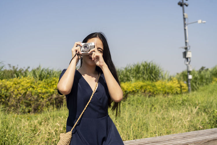 Woman photographing camera on field against sky