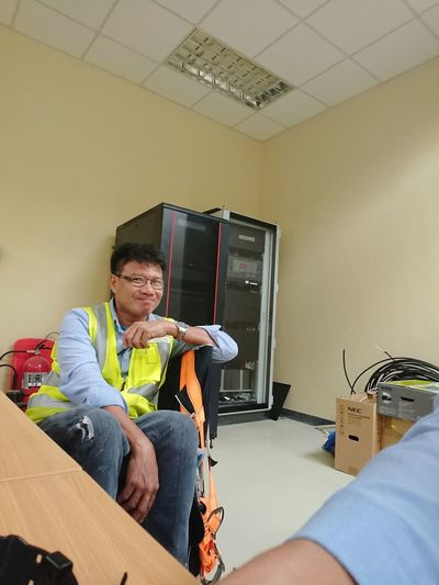 Portrait of smiling man in reflective clothing sitting at workplace
