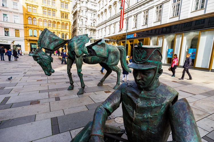 Statues on street amidst buildings in city