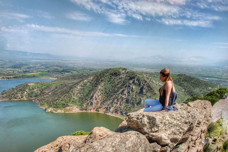 Woman sitting on rock looking at mountain against sky