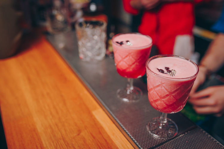 Close-up of drinks on table with people on background