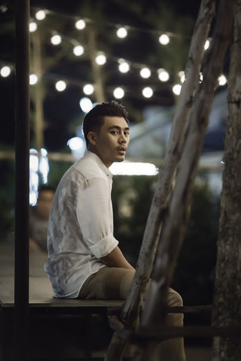 Side View Of Man Sitting In City At Night