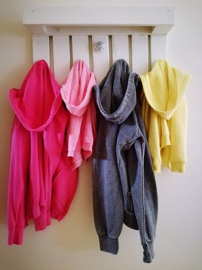 Close-up of hooded jackets hanging on hooks at home