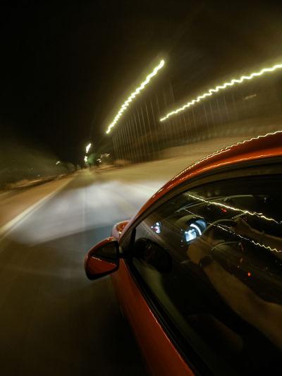 Car on illuminated street at night