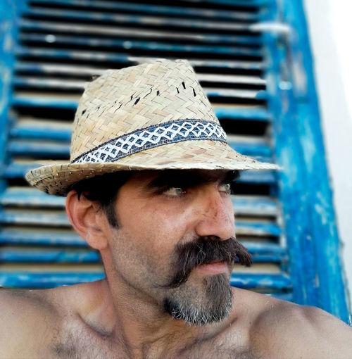 Close-up portrait of shirtless man wearing hat