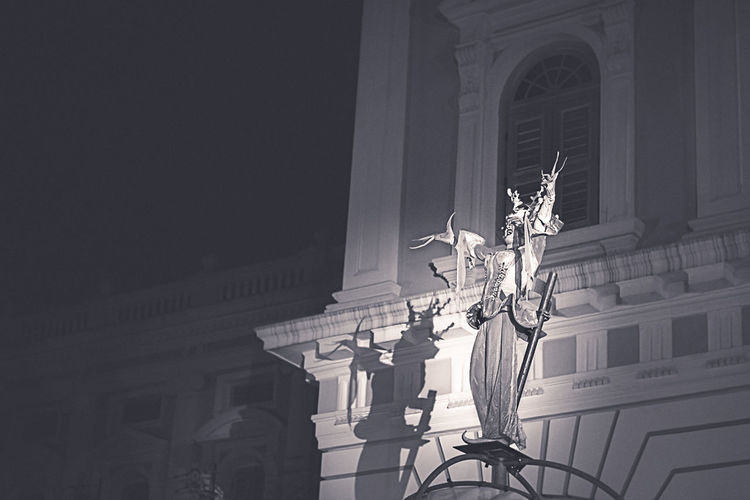 Low angle view of illuminated lamp by building at night