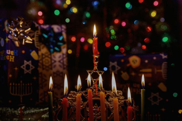 Close-up of illuminated candles against lighting equipment