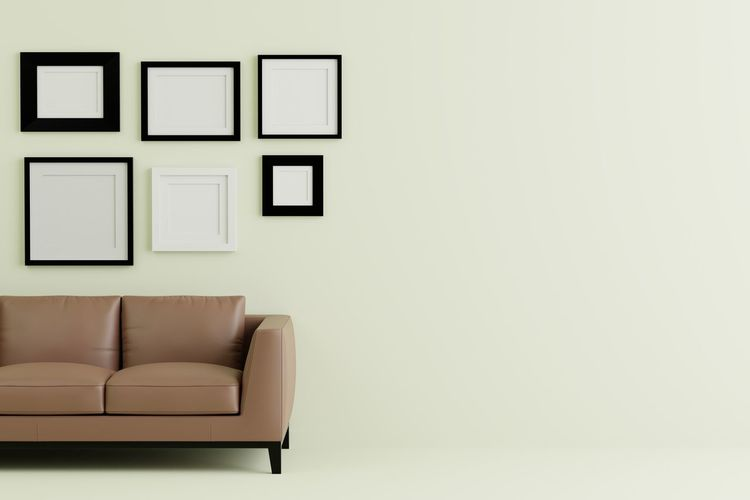 Empty Sofa Against Picture Frames On Wall