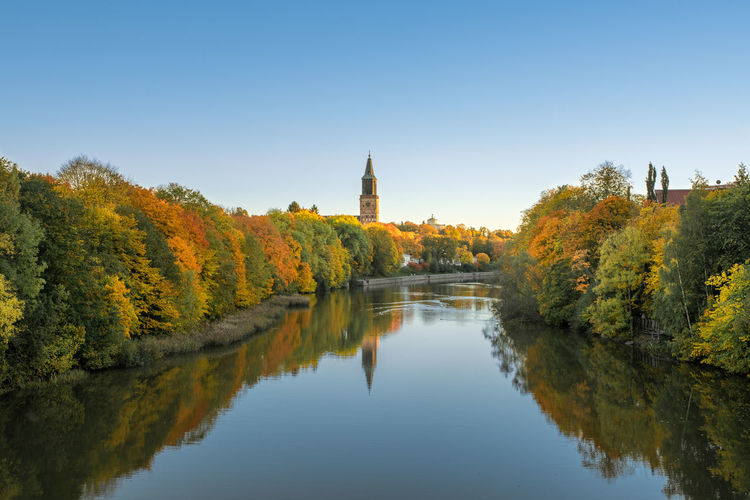 Scenic view of river amidst trees against clear sky during autumn