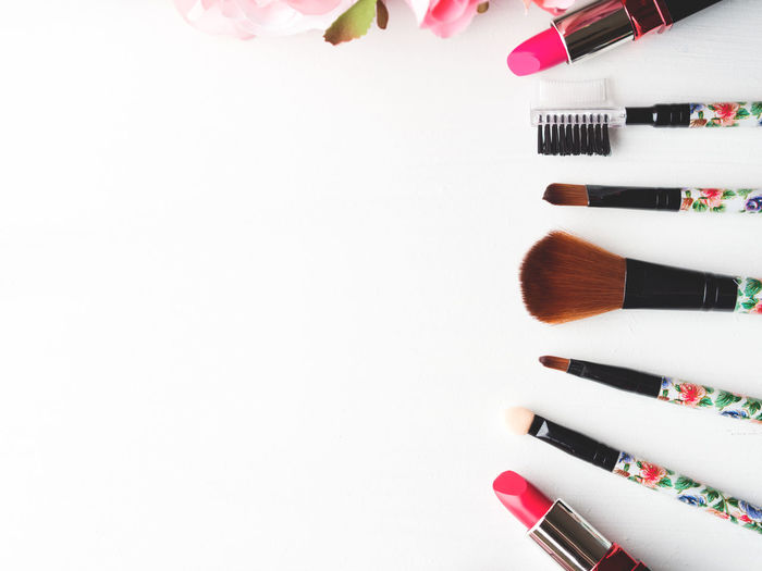 Close-up of make-up brushes with lipsticks on white background