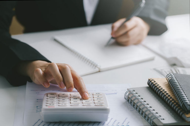 Woman hand using calculator and writing make note with calculate about finance accounting.
