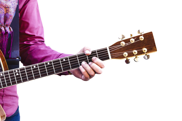 Low angle view of man playing guitar against white background
