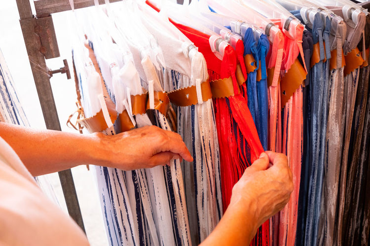 Midsection of man choosing textile in store