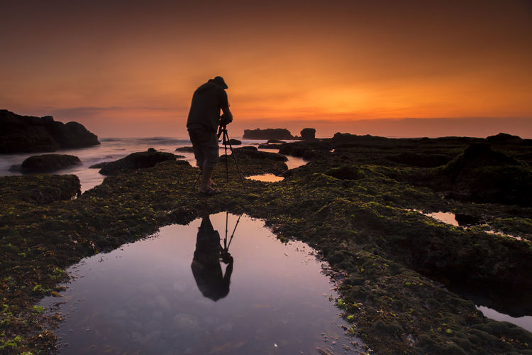 Silhouette man photographing while standing on rock by sea against sky during sunset