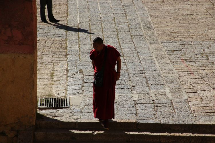 Tibetan Lama walking in the shadows. Tibetan Lama Walking Tribes In China Plateau Impression Belief Believein Searching Intersting A Shot Moment In Time Monk  Monk Tibet Shoot Autumn Scenics Hiking Trail Shadows & Lights Darkness Full Length Men Standing Shadow Pleading Monk - Religious Occupation