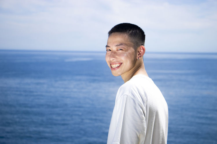 Portrait of smiling man standing in sea against sky