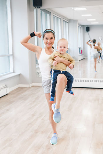 Full length of mother with son exercising on hardwood floor