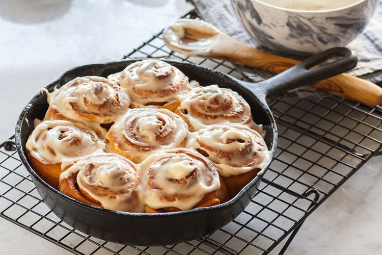 Iced Cinnamon Rolls or Buns in Cast Iron Skillet on Cooling Rack with Bowl of Frosting on Marble Counter Cinnamon Rolls Cinnamon Roll  Dessert Frosted Frosting Icing Roll Baked Baking Bowl Bun Cast Iron Skillet Cinnamon Cinnamon Bun Cinnamon Buns Food Gray Iced Kitchen Marble Nobody Pan Skillet Spoon Swirl