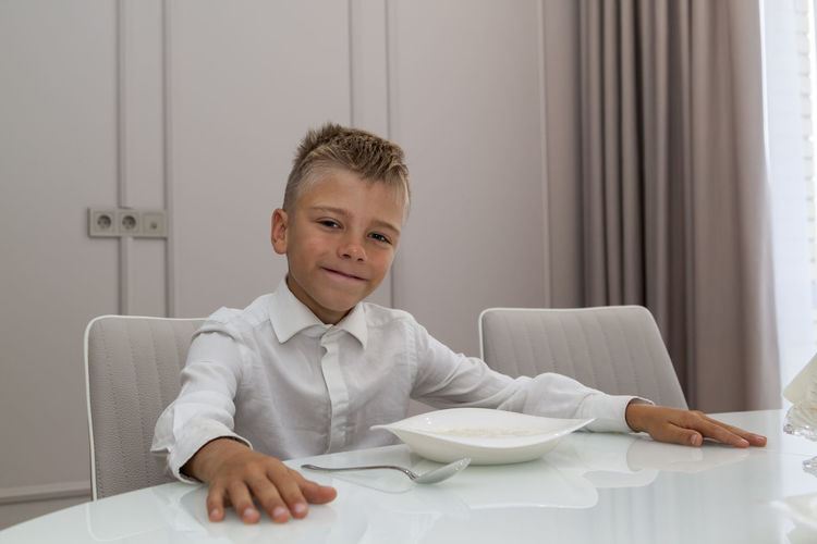 Portrait of smiling boy sitting by food on table at home