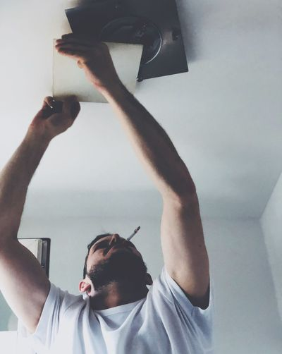 Man Smoking Cigarette While Opening Ceiling