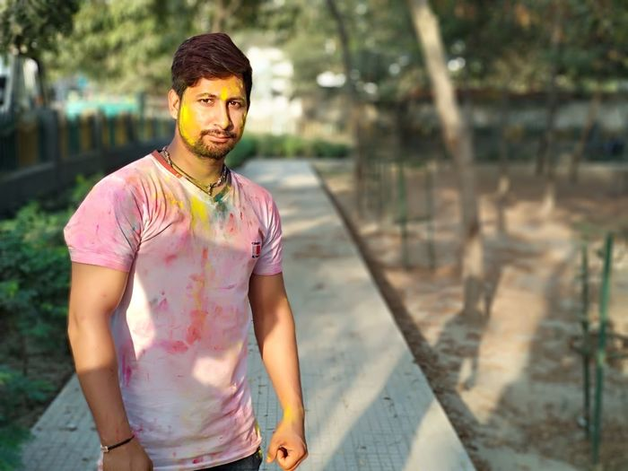 Portrait of young man smeared with multi colored powder standing on footpath