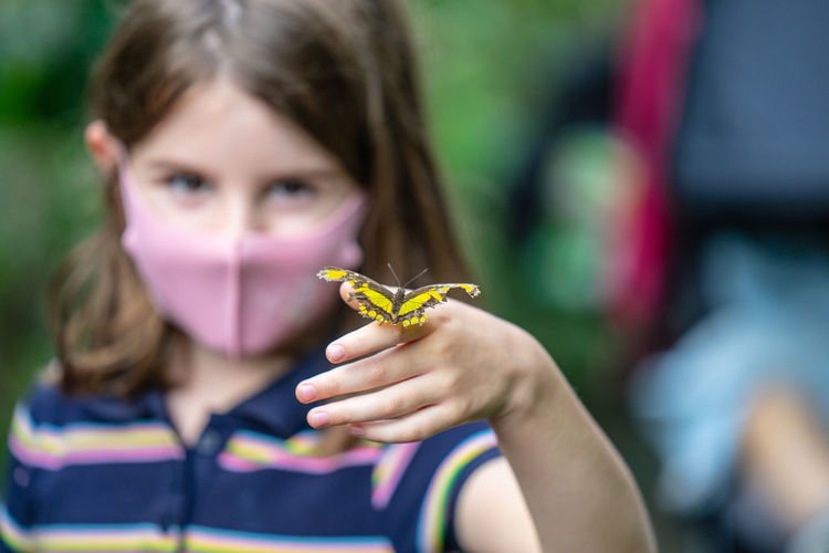Close-up portrait of girl holding butterfly outdoors