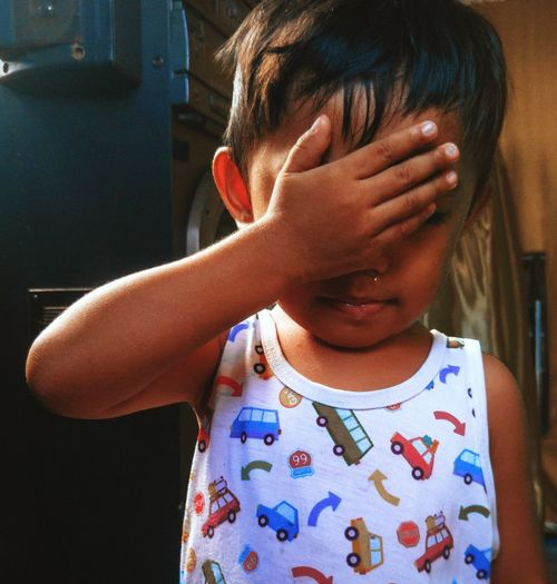 Close-up of baby boy covering face with hand while standing at home