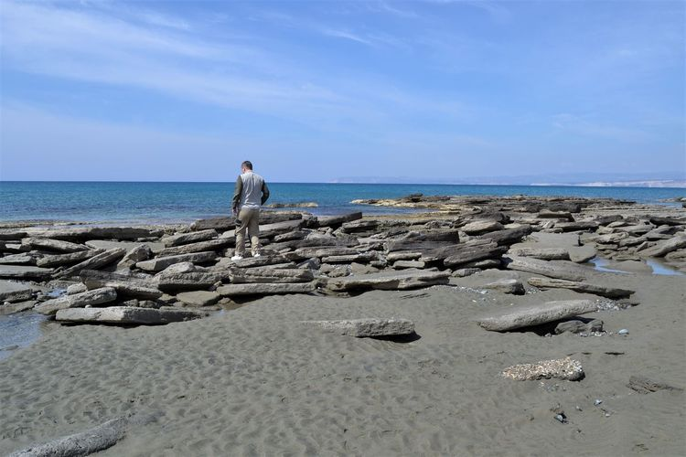 Back view of a man in casual clothing standing on an unusual rock formation at the beach during low tide at Shipwreck Cove, Akrotiri, Cyprus CY Beach Beauty In Nature Day Full Length Holiday Horizon Horizon Over Water Land Nature One Person Outdoors Pebble Rock Rock - Object Scenics - Nature Sea Sky Solid Standing Vacations Water