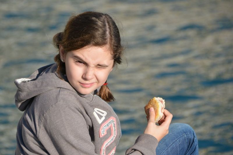 Portrait of cute girl holding food by lake