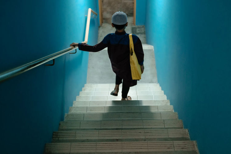 Rear view of boy moving down on staircase