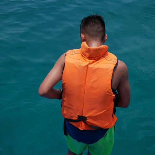 Rear view of man standing in sea