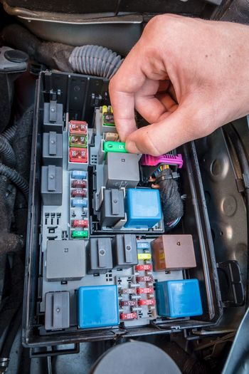 Hand checking a fuse in the fuse box of a modern car engine Car Checking Close-up Day Electric Parts Electricity  Engine Fuse Box Human Body Part Human Hand One Person Outdoors People Technology
