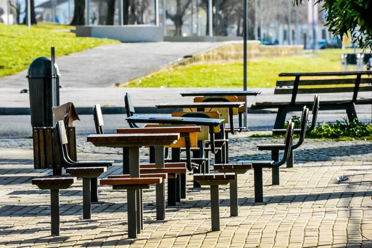 Empty chairs and table on footpath