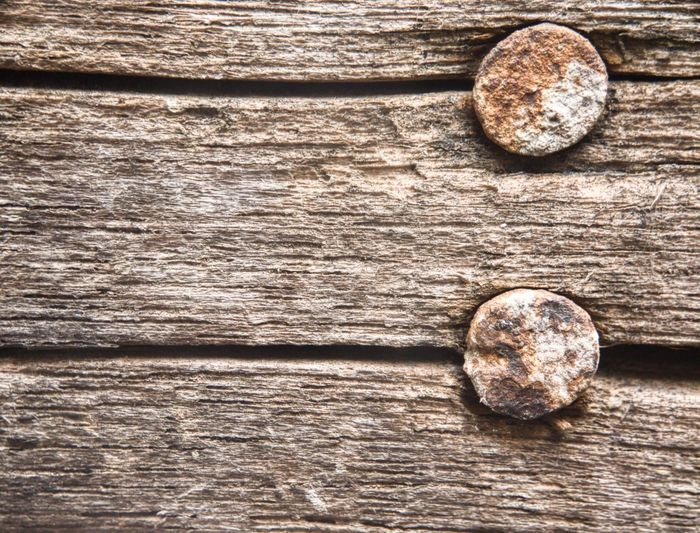 Close-up of rusty nails on wooden table
