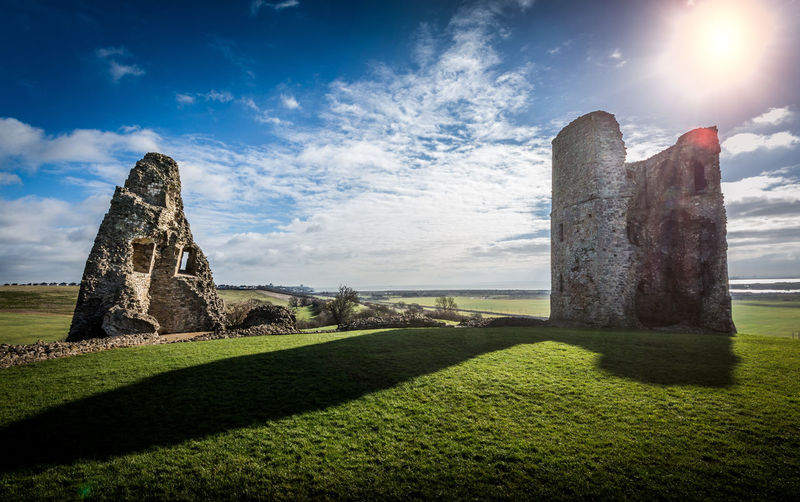 Sun shining over old ruins on grassy field
