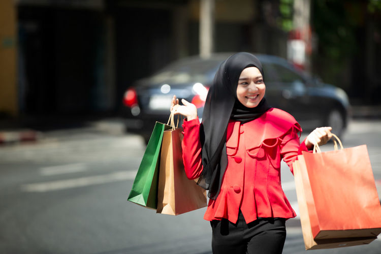Smiling young woman holding shopping bags standing on street in city
