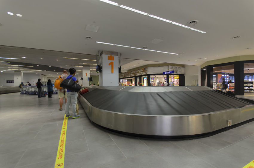Unknown male at luggage claim line in airport. Airport Airport Trolley Baggage Claim Floor Indoors  International Luggage Luggage Cart  Luggage Trolleys Luggage, Travel  Motion People Pushing Sign Signage Trolley Waiting