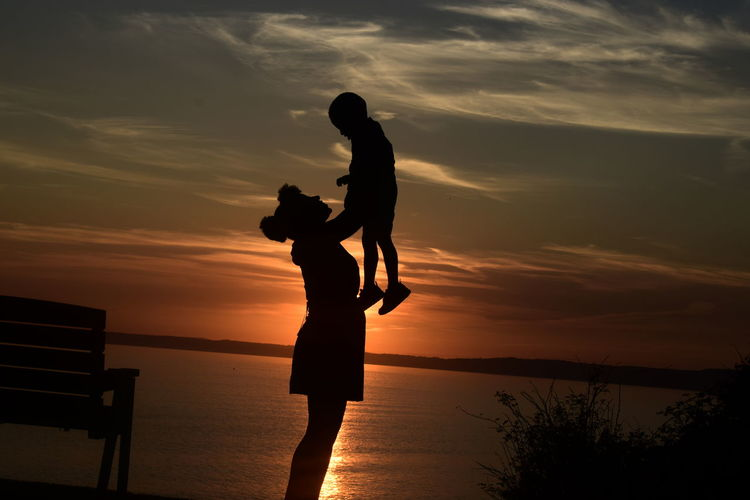 Silhouette Mother Lifting Son While Standing At Beach Against Sky During Sunset