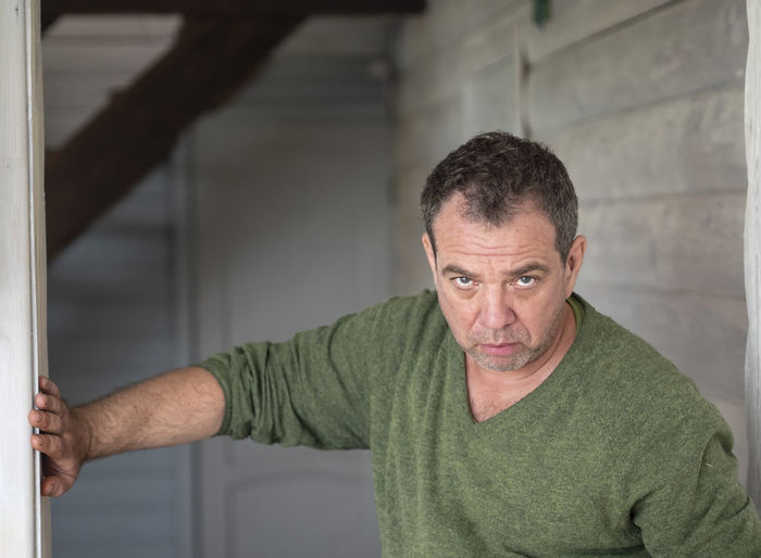 Portrait of serious mature man leaning on wall at home