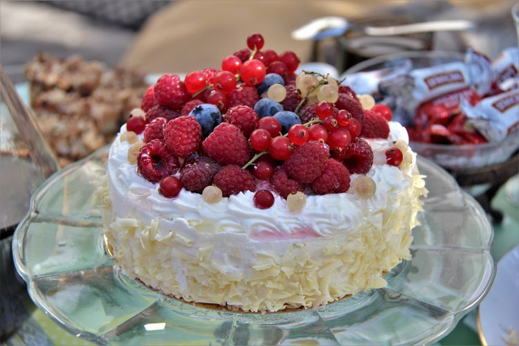 Close-Up Of Berry Fruits On Cake At Table