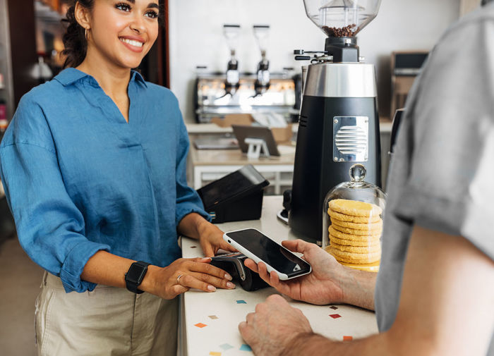 Midsection of customer making nfc payment at cafe